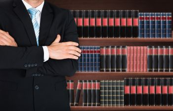 Lawyer Posing in Front of Shelf of Law Books