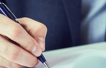 Hand of businessman in suit filling and signing with blue pen