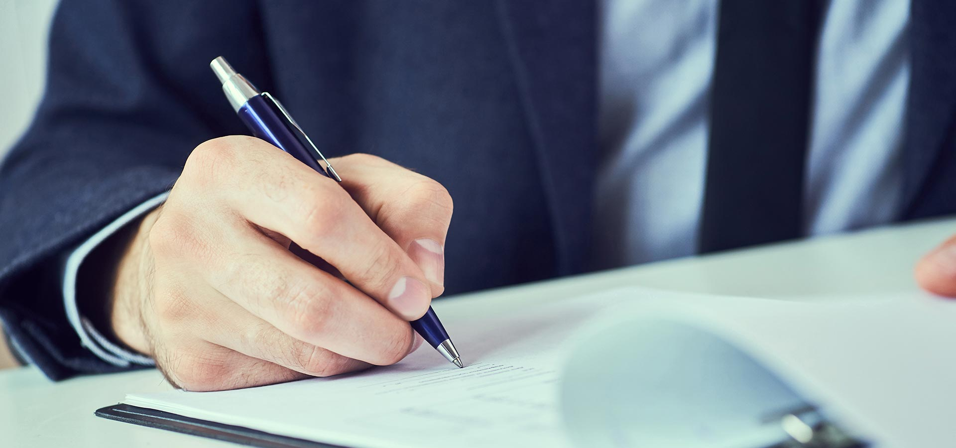 a hand signing a document with blue pen